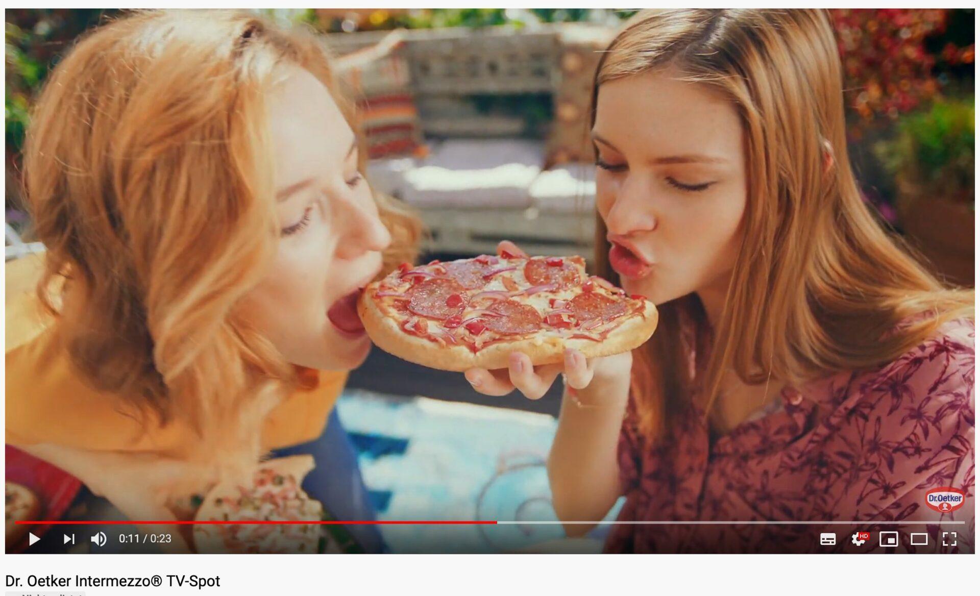 Frauen beißen in eine Mini-Pizza