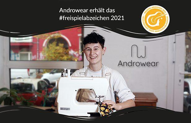 Androwear-Gründerin Isabelle Merten sitz an einer Nähmaschine und näht bunte Unterwäsche, sie lacht fröhlich in die Kamera. Oben und unten sind schwarze Wellen illustriert, oben steht in weißer Schrift: Androewar erhält das freispiel-Abzeichen 2021.